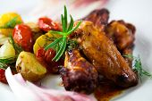 foto of chicken wings  - Roasted chicken wings with baked potatoes and tomatoes - JPG