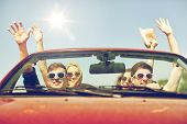 leisure, road trip, travel and people concept - happy friends driving in cabriolet car at country an poster