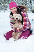 Happy woman with dog in winter forest