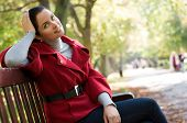 Young Caucasian woman sitting in a park on a wooden bench,