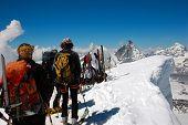 backcountry skiesr (ski touring) on background the Matterhorn, west alps, Europe.