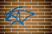 Photo of a plain red brick wall with a blue graffito