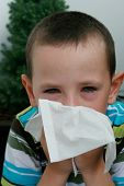 Five years old boy with tissue blowing his nose. Child with allergy, conjunctivitis and black rings