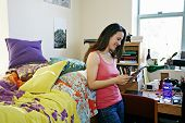 Mixed race college student using tablet computer in dorm poster