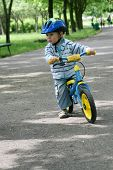 19 months old baby boy riding on his first bike in a helmet. Bike without pedals. Child learning to