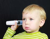 2 years old baby boy waits for a digital thermometer to determine his temperature.
