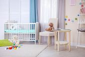 Interior of light cozy baby room with crib and bedding poster