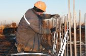 worker in workwear making reinforcement metal framework lattice for concrete pouring