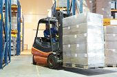 stock photo of forklift driver  - Forklift loader moving at warehouse with a cardboard boxes - JPG