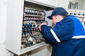 One electrician working on a industrial panel mounting, assembling, adjusting new voltage wiring