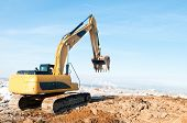Heavy excavator loader at winter frozen soil moving works in sandpit