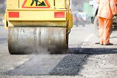 Young builder on Asphalting paver machine during Road street repairing works