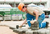 stock photo of pecker  - mason worker making sidewalk pavement with stone blocks - JPG