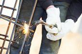 Постер, плакат: крупный план рабочих рук в защитные перчатки резка бетона армирующие металлических стержней в строительстве s