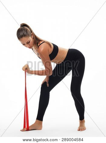 poster of Motivation, fitness and people concept: Sporty woman  doing a exersize  with resistance band. Photo