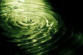 Drop rippled in dark green water. Matrix color style.