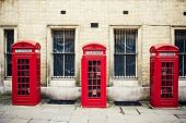 Three red phone boxes over grunge wall background