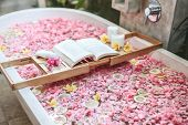Bath tub with flower petals and lemon slices. Book and candles on a tray. Organic spa relaxation in  poster