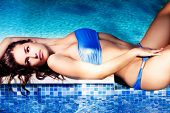 woman in blue bikini lie by the pool, summer day