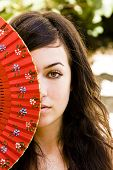 Spanish green eyed woman behind traditional fan.