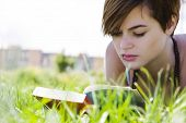 Young beautiful blonde reading over the grass