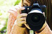 Olho de jovem mulher por trás da câmera slr.