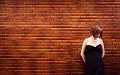 Sad woman portrait posing over red brickwall