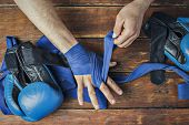 Man Bandage Boxing Tape On His Hands Before The Boxing Match On A Wooden Background. The Concept Of  poster