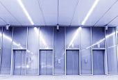 Four closed elevators in modern blue tone.