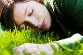 Young woman dreaming on the grass