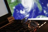 Tracking A Hurricane portrayed by eye glasses atop a laptop computer - Hurricane image in background
