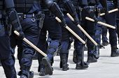 Carrying a big stick - Police Officers in full riot gear march toward the violence.