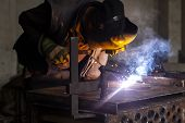 Man Welds Metal. Worker Welding Steel In Industry With Safety Mask Safety Gloves And Safety Equipmen poster