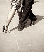 Street dancers performing tango dance. Aged tone.