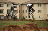 Double jump - two males riding bikes launch high into the air over earthen berms.