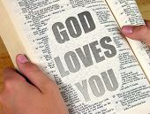Getting the message - The words 'God Loves You' appearing on a page from the Bible.