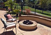 Custom Home backyard patio with two empty chairs overlooking a firepit, custom hardscape and golf course view.