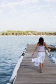Young beautiful woman walking on pier