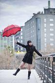 Young happy girl dancing under rain