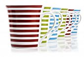 Red, green and blue mugs on a white background with space for text