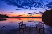 Two Wooden Bench Or Chairs On A Wood Dock Facing A Lake At Sunset In Finland poster