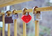 Door Locks Hanging On A Metal Fence On A Bridge Of Love. Selective Focus On One Padlock In Shape Of  poster