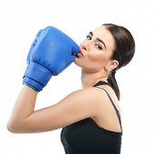 Sporty girl doing boxing exercises. Photo of young woman kisses her boxing gloves  isolated on white poster