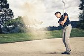 Male golfer in blue shirt and grey pants hitting golf ball out of a sand trap with sand wedge and sand caught in motion.