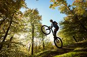 Silhouette Of Athlete Cyclist Standing On Back Wheel On Trial Bicycle. Professional Sportsman Making poster