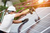 Professional Technician Working With Screwdriver Connecting Blue Shiny Solar Photo Voltaic Panel To  poster