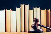Court hammer and books on black background. Court chambers, office of judge. Law and trial. poster