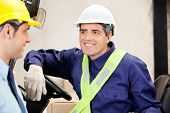 pic of forklift driver  - Happy forklift driver looking at male supervisor - JPG