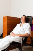 Young man relaxing in spa hearing music with headset in quiet room