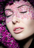 Close up portrait of model with flowered wreath and fashion makeup with eyes shut
